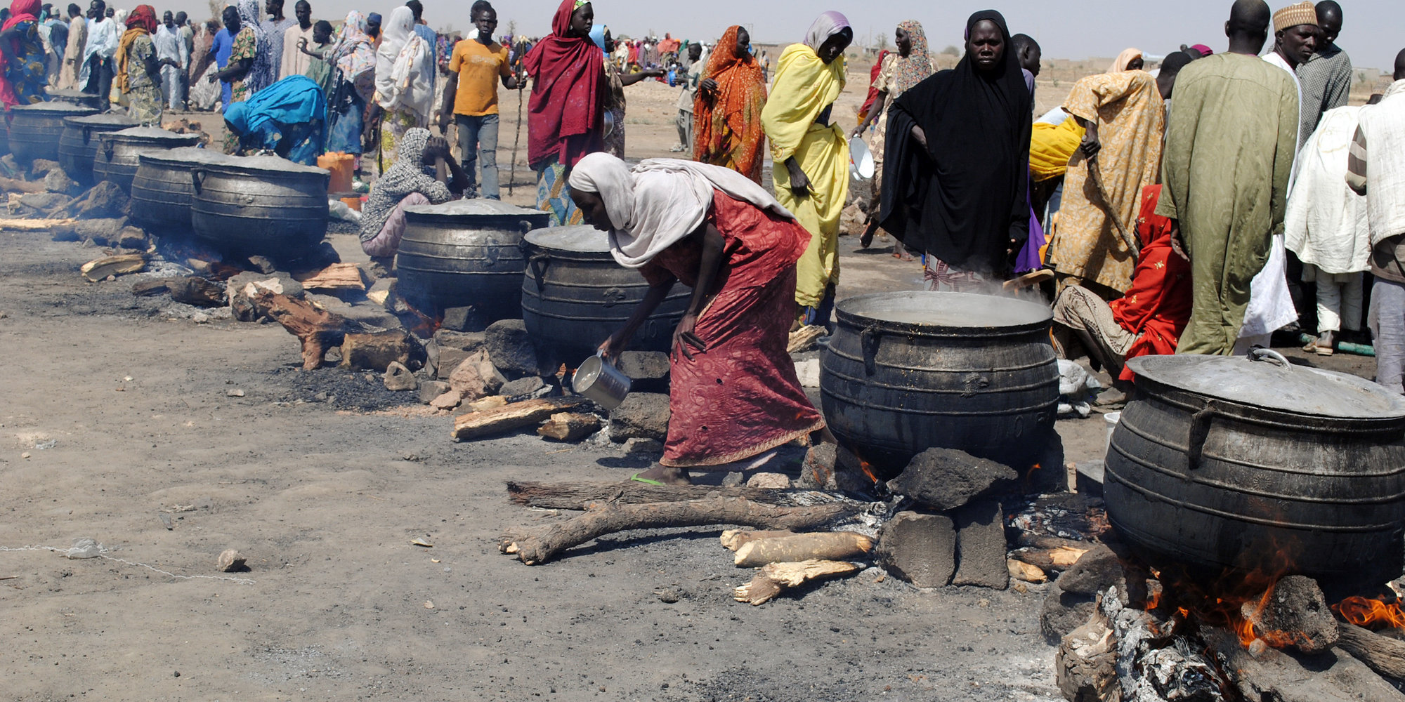 Women cook in pots heated up with firewood at an Internally Displaced Persons (IDP) camp at Dikwa, in Borno State in north-eastern Nigeria, on February 2, 2016. The National Emergency Management Agency in collaboration with Borno State Emergency Management Agency has set up new IDP camps in Ngala, Marte, Bama and Mafa councils to decongest the growing population of IDP camp set up at Dikwa council of Borno State. Nigeria expects many of the 2.1 million people internally displaced by Boko Haram's insurgency to return home in the coming year, amid claims the Islamists are in disarray and a spent force. / AFP / STRINGER        (Photo credit should read STRINGER/AFP/Getty Images)