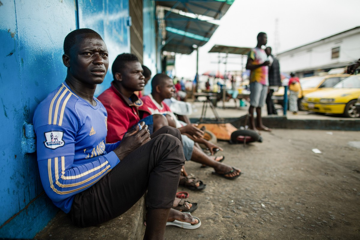 Ebola Outbreak in West Africa  Monrovia, Liberia - September 19, 2014:   Former taxi drivers in Monrovia. Vincent, 24 (in blue) and Junior, 20 (in red), both residents of West Point used to drive motorcycles for a living -- a form of local transport in Liberia used like taxis. After the government banned motorcycles in downtown Monrovia they had to stop. Now, because of Ebola, they can't find any work. They want a job, but no one is hiring so they wait on the side of the street at the entrance of West Point. They are not happy with the government and their response to Ebola. They want a change in leadership. Photo by Morgana Wingard    Source: Flickr Album ' Ebola Outbreak in West Africa': The Ebola health crisis that has claimed thousands of lives must not be allowed to become a crippling socio-economic crisis as well. Now is the time to ensure these countries can also continue to function and swiftly get back on their feet - see how UNDP is supporting this.           https://www.flickr.com/photos/37913760@N03/sets/72157648119364049/with/16187510217/ Photo: UNDP/Morgana Wingard